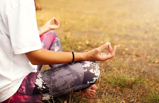 Pretty woman facendo esercizi di yoga nel parco