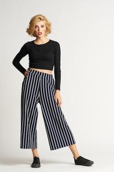 Pretty woman in maglione nero a righe pantaloni vestiti di moda sfondo chiaro studio.