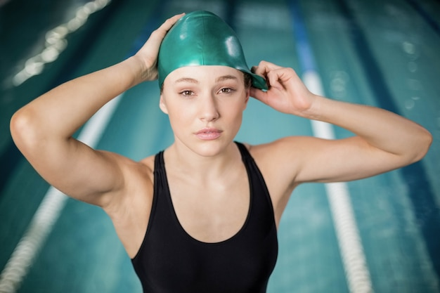 Pretty woman regolando il suo cappello da bagno in piscina