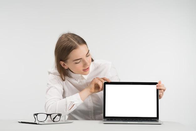 Pretty woman si siede al tavolo e guardando lo schermo. concetto di mockup