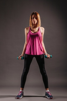 Pretty woman with dumbbells