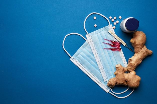 Prevenire il coronavirus. maschera medica, termometro, vitamine, siringa su sfondo blu.