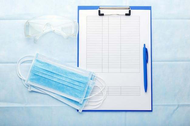 Prevenzione coronovirus, modulo di analisi del test covid-19. maschera chirurgica per il viso, documenti medici, occhiali protettivi sul posto di lavoro dei medici.