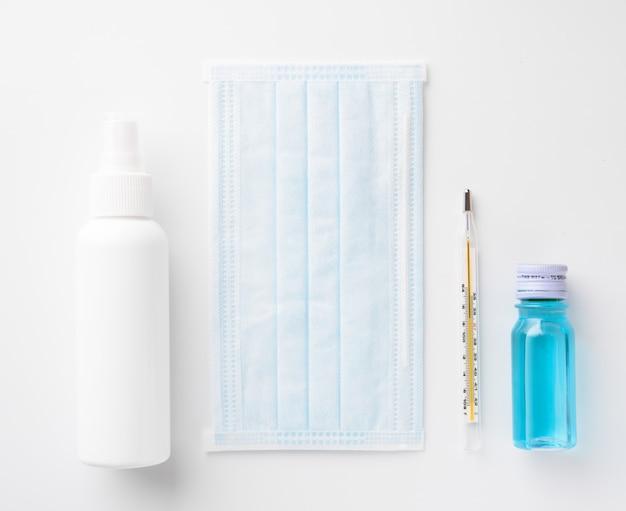 Prevenzione del coronavirus con mascherina chirurgica medica, disinfettante per le mani, gel per alcool e termometro, vista dall'alto