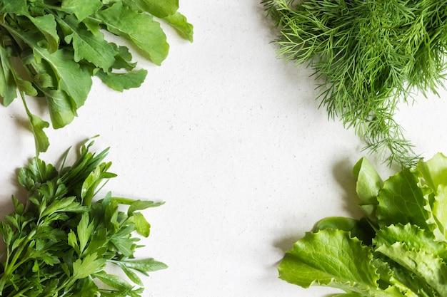 Prezzemolo, aneto, rucola e lattuga. il concetto di alimentazione sana. copia spazio al centro.