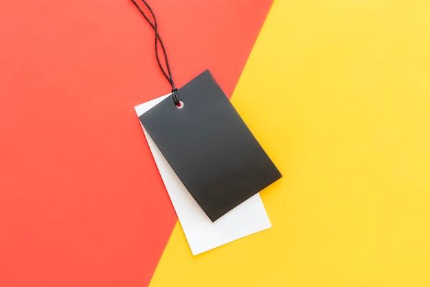 Prezzo da pagare isolato dei vestiti con lo spazio della copia sul fondo rosso e giallo rosso di colore.
