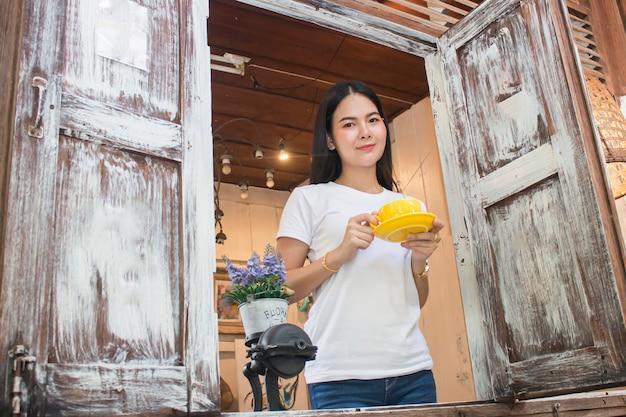 Prima colazione bevente del caffè di donna asiatica di mattina in finestra
