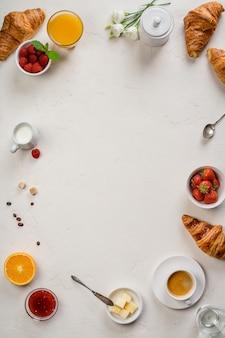 Prima colazione continentale sul fondo bianco della tavola, vista superiore