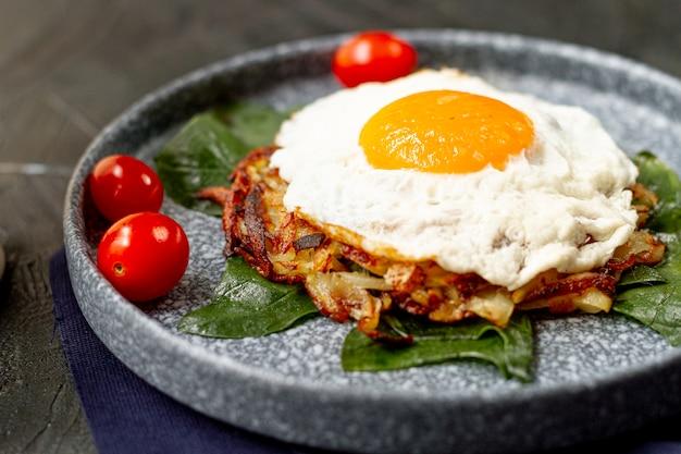 Prima colazione dell'uovo fritto con i pomodori e i browns dell'hash