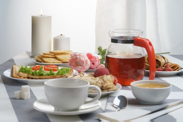 Prima colazione fresca e saporita con un panino e un tè su una priorità bassa chiara.