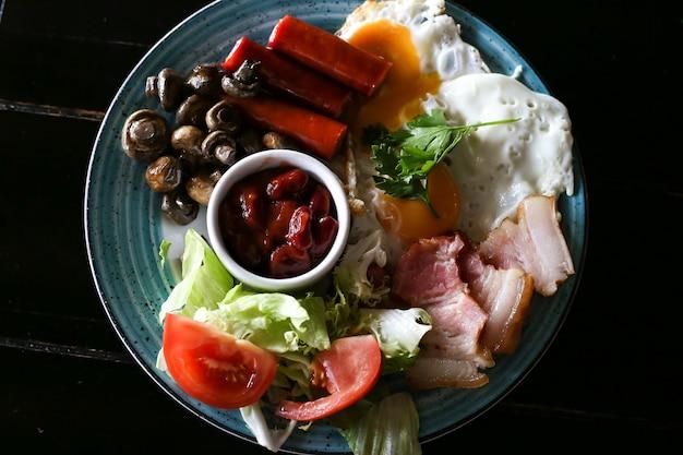 Prima colazione inglese completa con le uova fritte su legno