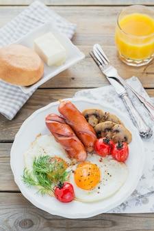 Prima colazione inglese con uova fritte, salsicce, funghi, pomodori grigliati e succo d'arancia fresco sul tavolo in legno rustico. vista dall'alto