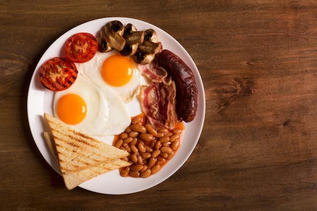 Prima colazione inglese su una tavola di legno bianca