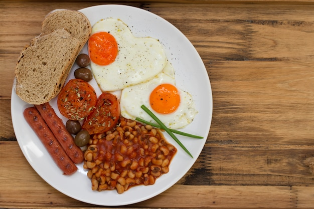 Prima colazione inglese sul piatto bianco sulla tavola di legno marrone