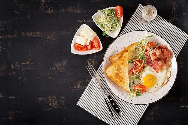 Prima colazione inglese - toast, uova, pancetta e pomodori e insalata di microgreens. vista dall'alto. distesi