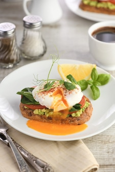 Prima colazione. le migliori uova alla benedict su una fetta di pane ai cereali tostato con guacamole e spinaci
