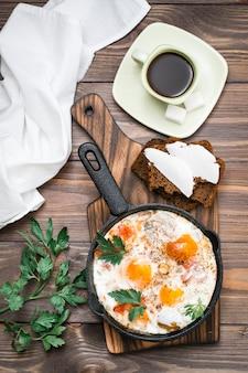 Prima colazione pronta: shakshuka da uova fritte con pomodori e prezzemolo in una padella, pane con burro e caffè su un tavolo di legno. vista dall'alto