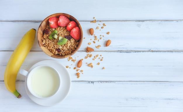 Prima colazione sana, cereali muesli con latte e banana