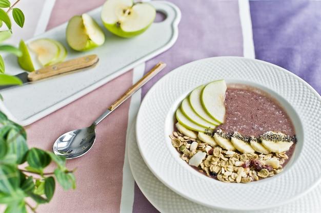 Prima colazione sana, ciotola di frullato con banana, mela, semi di chia, muesli e yogurt.