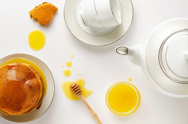Prima colazione sana con i pancake e il miele casalinghi di dieta su fondo bianco