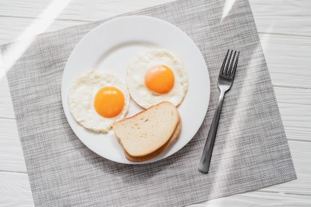 Prima colazione sana con le uova fritte sulla tavola di legno