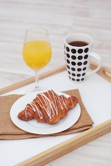 Prima colazione. tazza di tè, croissant e un bicchiere di succo.