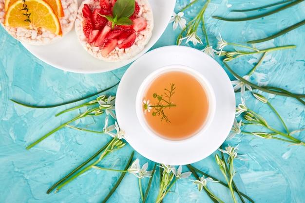 Prima colazione - tè, pane croccante del riso con frutta fresca sull'azzurro.