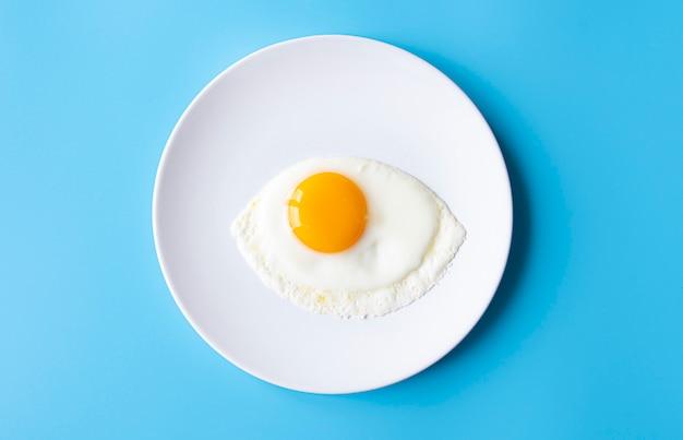 Prima colazione, uovo fritto, tuorlo, omelette sul piatto bianco con la tavola di colore, immagine creativa