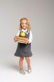 Prima elementare con libri e una mela sorridente su uno sfondo luminoso