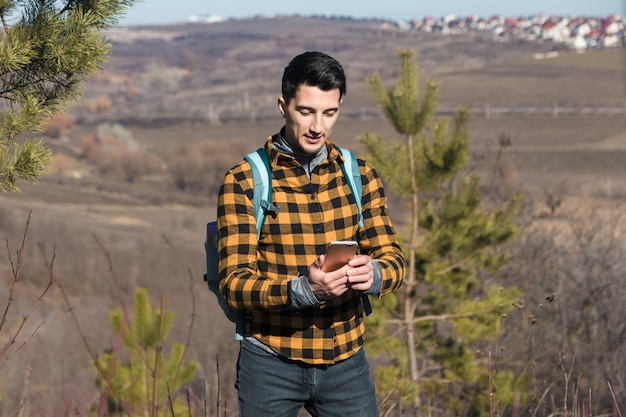 Primavera all'aperto. bell'uomo in campagna utilizzando il telefono per navigare