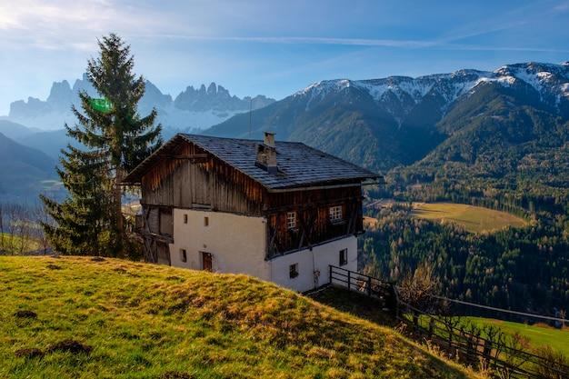 Primavera nelle dolomiti. una vista delle case in piedi sui pendii verdi della montagna. villaggi san pietro e santa maddalena.