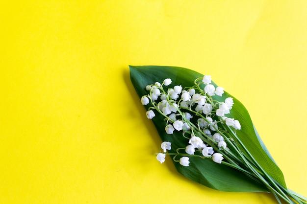 Primavera o estate. bouquet di mughetto sullo sfondo giallo. vista dall'alto. copia . fiori di primavera .