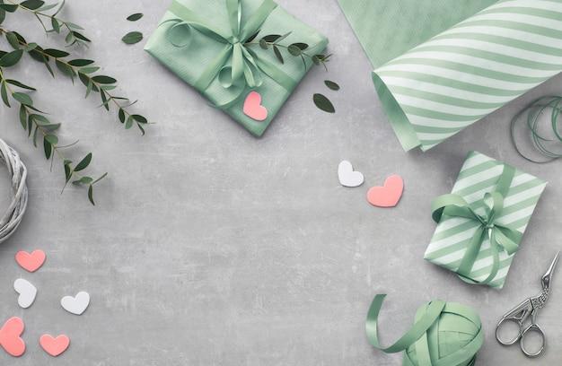 Primavera piatta distesa con scatole regalo, cuori e foglie di eucalipto