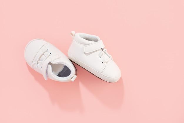 Prime scarpe del bambino su fondo pastello rosa. concetto di famiglia o maternità.