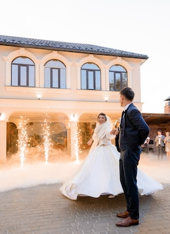 Primo ballo di sposi innamorati all'aperto circondato da effetti pirotecnici