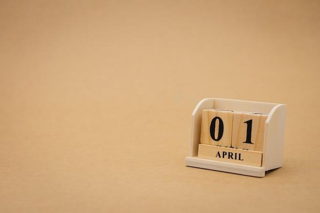 Primo calendario di legno di aprile su fondo astratto di legno d'annata. primo d'aprile