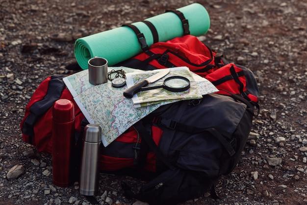 Primo colpo di attrezzatura da viaggio, zaino, mappa, bussola, coltello, materassino a terra