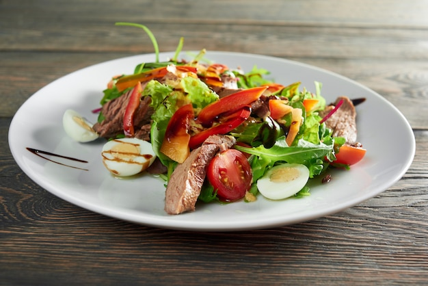 Primo colpo di gustosa insalata fresca con carne alla griglia e uova e salsa verde pepe delizioso mangiare nutrizione sana pranzo cena cena cucina cucina ricetta ingredienti.