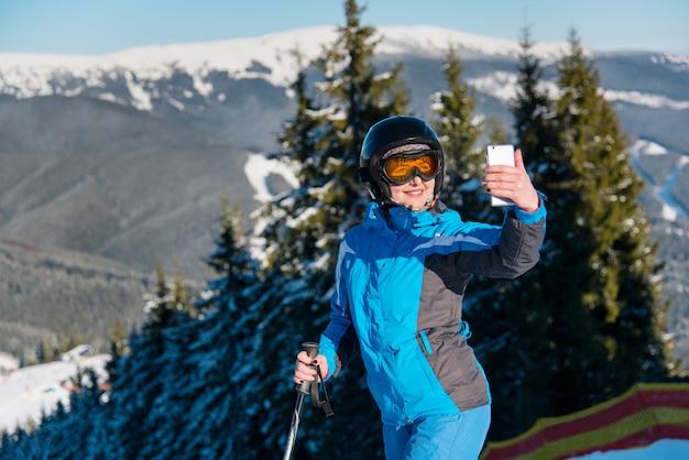 Primo colpo di uno sciatore donna sorridente prendendo un selfie con il suo smart phone mentre sciare in montagna presso la stazione sciistica in una giornata invernale di sole