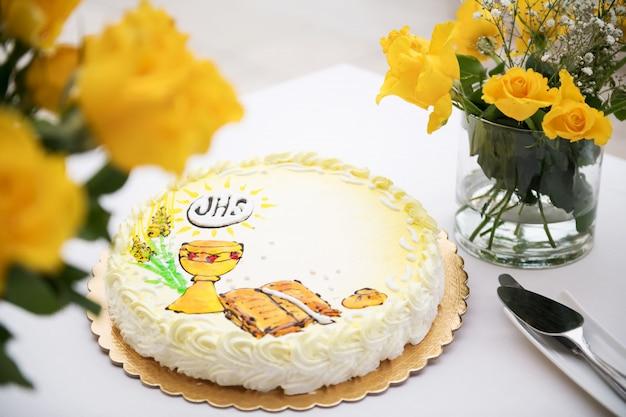 Primo concetto di santa comunione, bella torta con prima santa comunione e rose gialle su un tavolo bianco