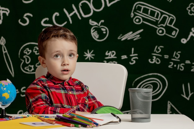 Primo giorno di scuola. ragazzo del bambino della scuola elementare. di nuovo a scuola. il ragazzino raccoglie lo zaino della scuola a scuola. bambino della scuola elementare.