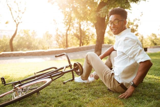 Primo mattino bello giovane africano con la bicicletta