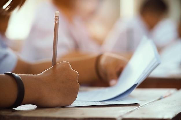 Primo piano a disposizione della matita della tenuta dello studente e della presa dell'esame in aula con lo sforzo per la prova di istruzione.