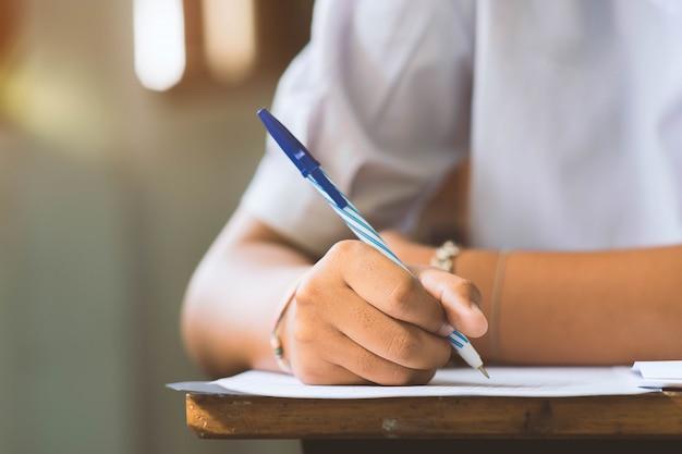 Primo piano a disposizione della penna di tenuta dello studente e l'esame in aula con lo stress per il test di educazione.