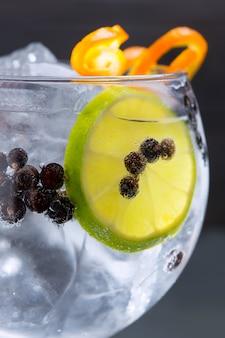 Primo piano a macroistruzione del cocktail tonico del gin con le bacche di ginepro