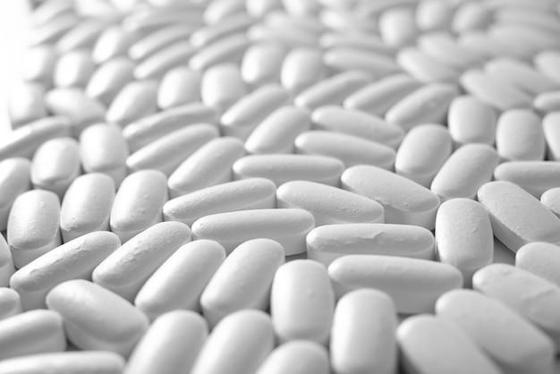 Primo piano a macroistruzione di molte pillole bianche, concetto del farmaco