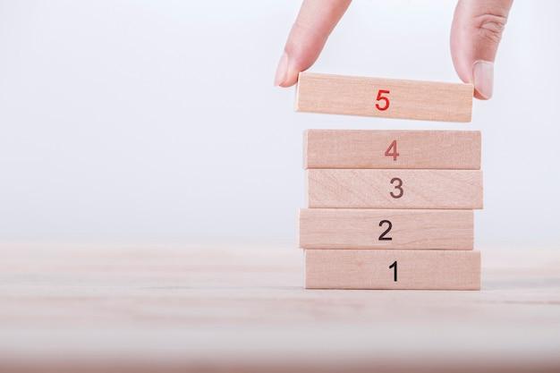 Primo piano a mano scegliere una valutazione del numero cinque con cima alta