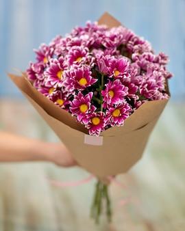 Primo piano a portata di mano che tiene il mazzo di fiori