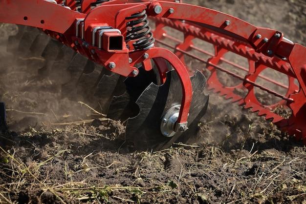 Primo piano agricolo dell'aratro sulla terra, macchinario agricolo.