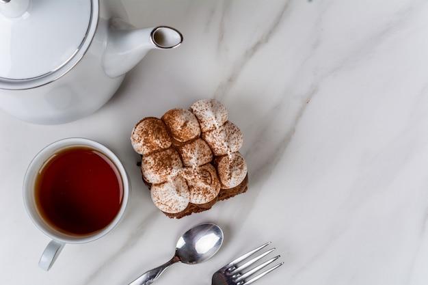 Primo piano alla deliziosa mini torta al cioccolato con una tazza di tè. concetto di cuoco e prodotti da forno.